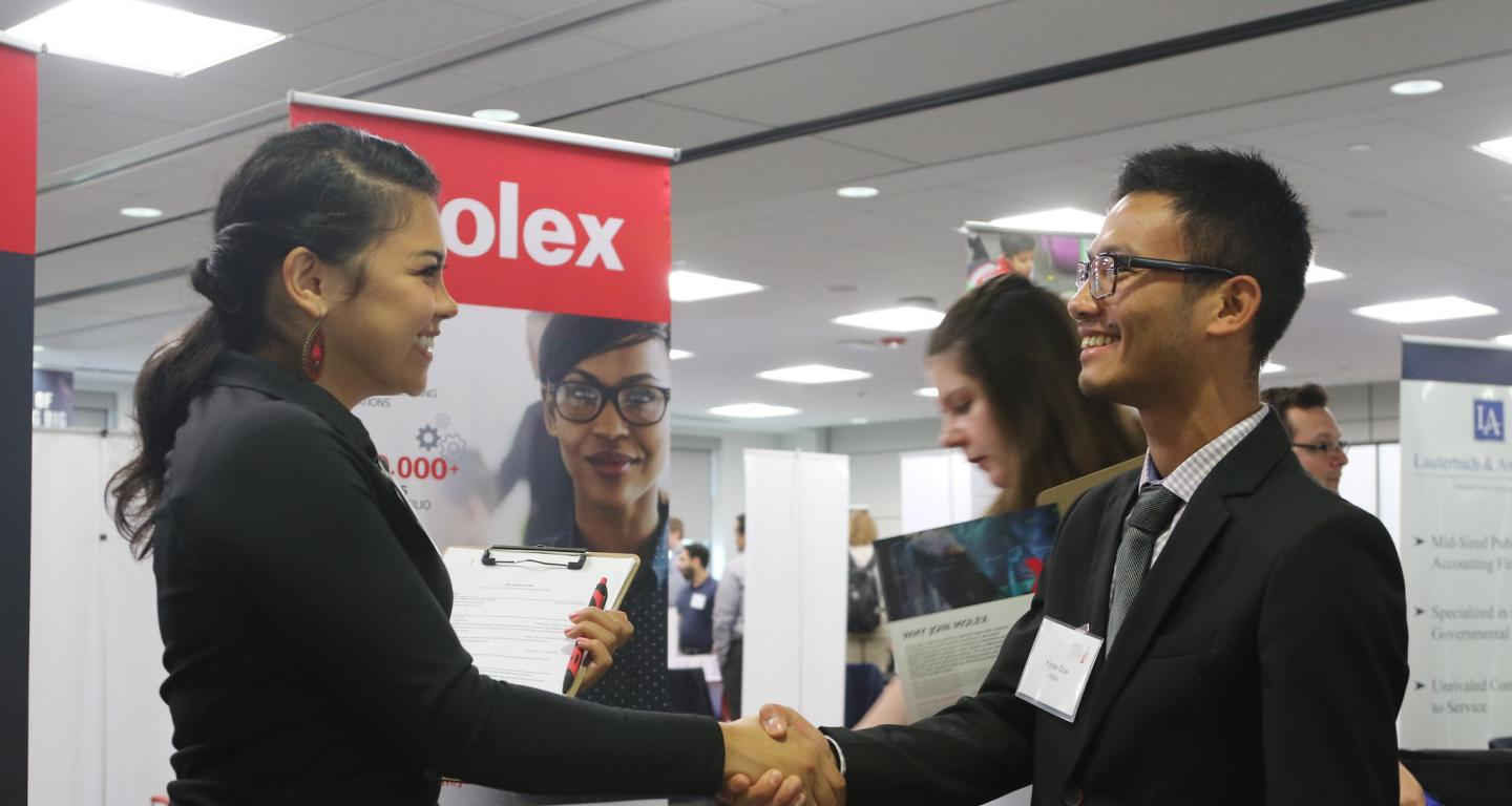 A student shakes hands with a potential employer for a chance at post-college careers.