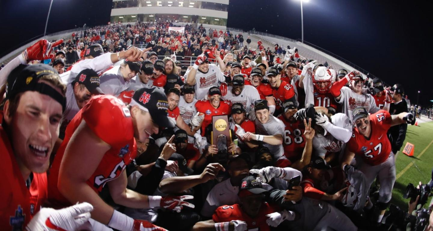 The North Central College football team celebrates with the national title trophy.