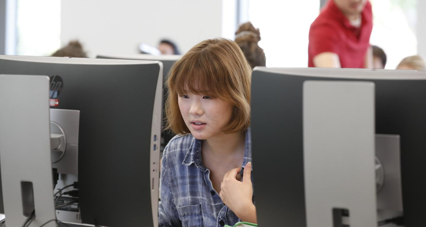 A student at a computer researching schools like North Central College.