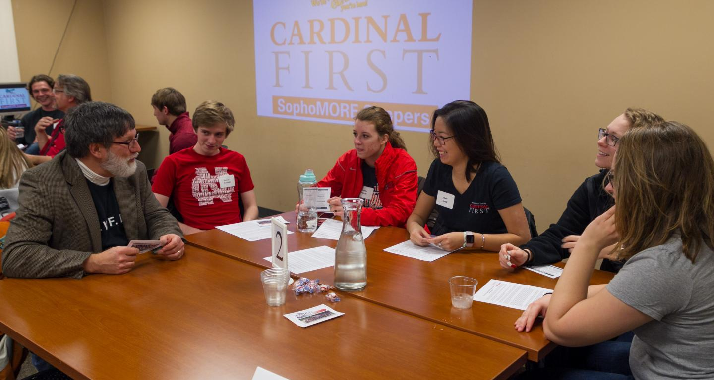 Students discussing the best way to impress professors at a Cardinal First event.