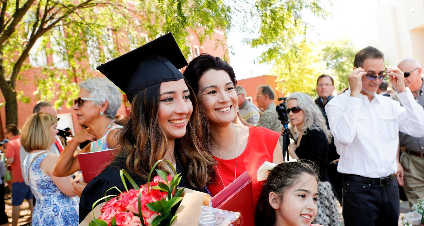 A Cardinal First graduate with her mother and sister at graduation.