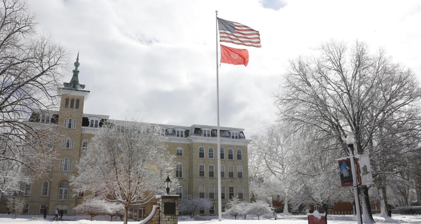 Old Main flying American Flag and College Flag in Winter