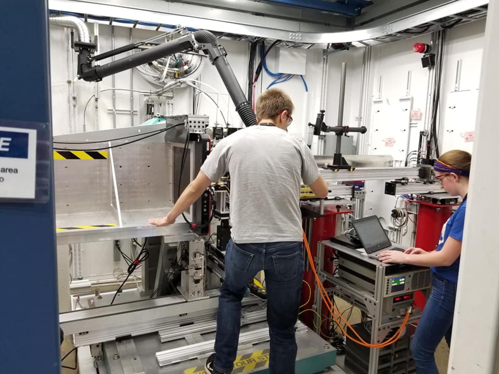 Samuel Lee and Morgan Fellows replace ionic liquid samples on the X-ray instrument.
