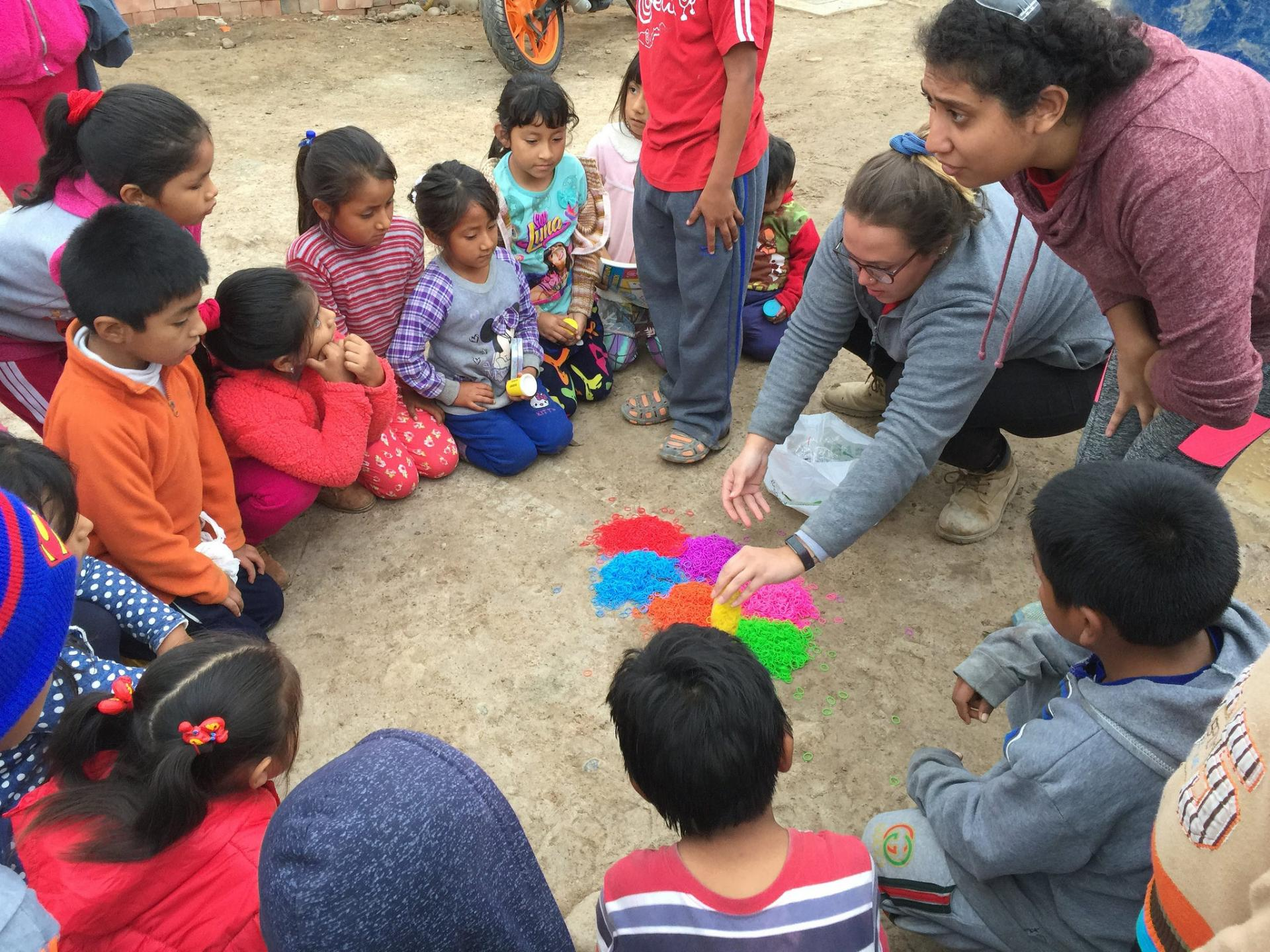 Maria Requena plays a game with children in La Florida.
