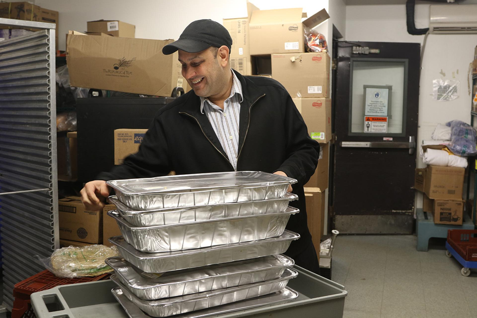 Chartwells employee helps load food for donation.