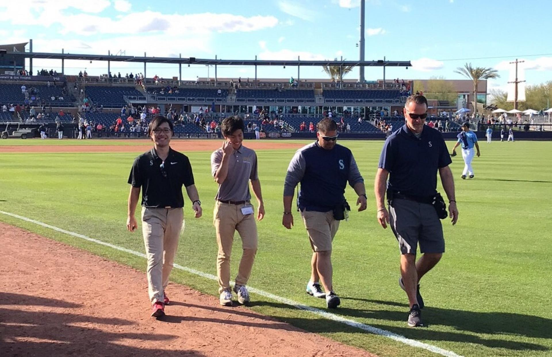 Shota Sato and Seattle Mariners' athletic trainers walk on the field