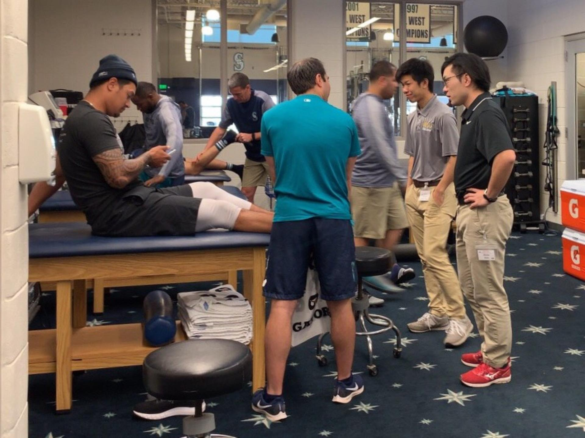 Athletic trainers in the athletic training room with players.