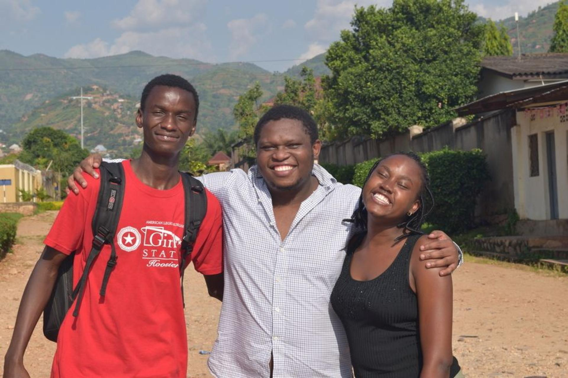 Gates Cambridge Scholar Etienne Mashuli poses with two of his students.
