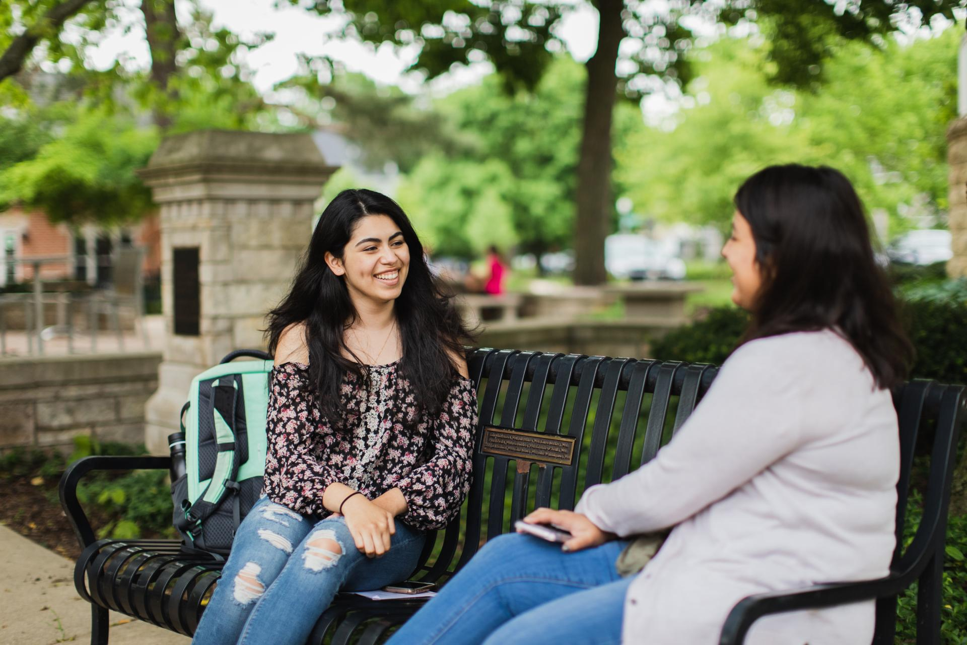 Two students talking on a campus bench