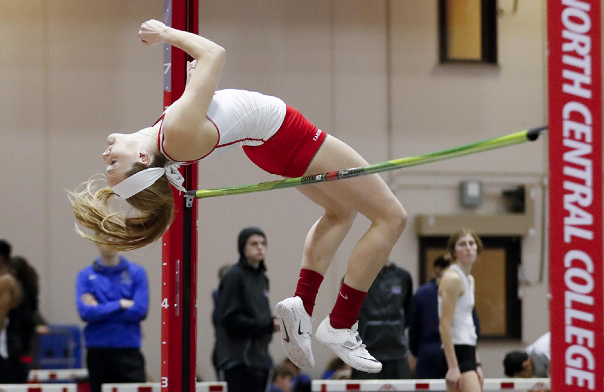 High jumper Taiah Gallisath clears the bar during a North Central College women's track meet.