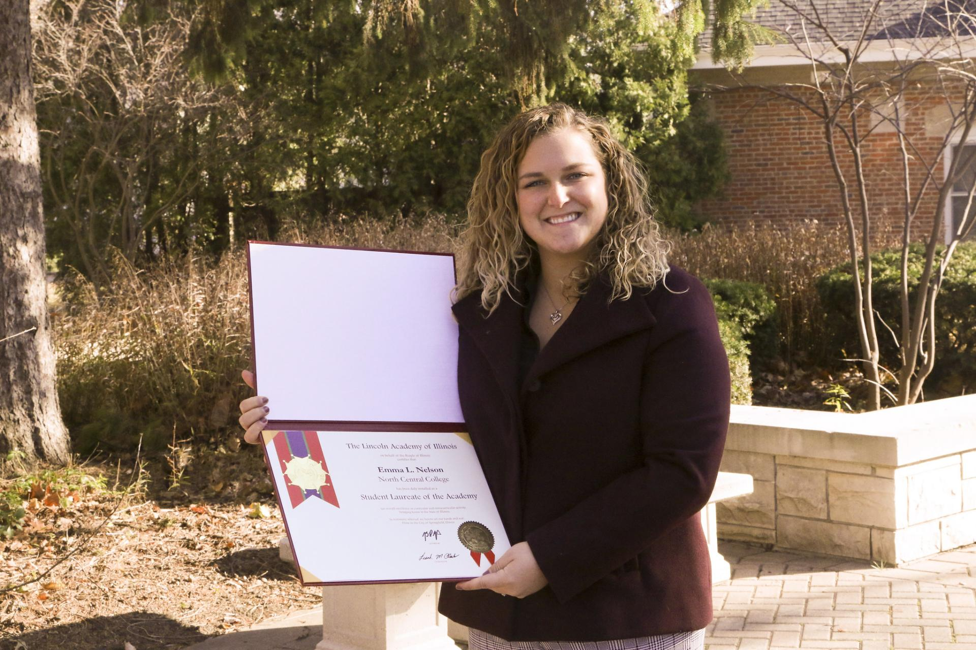 Emma Nelson holds her certificate for being North Central College's 2020 Lincoln Laureate.