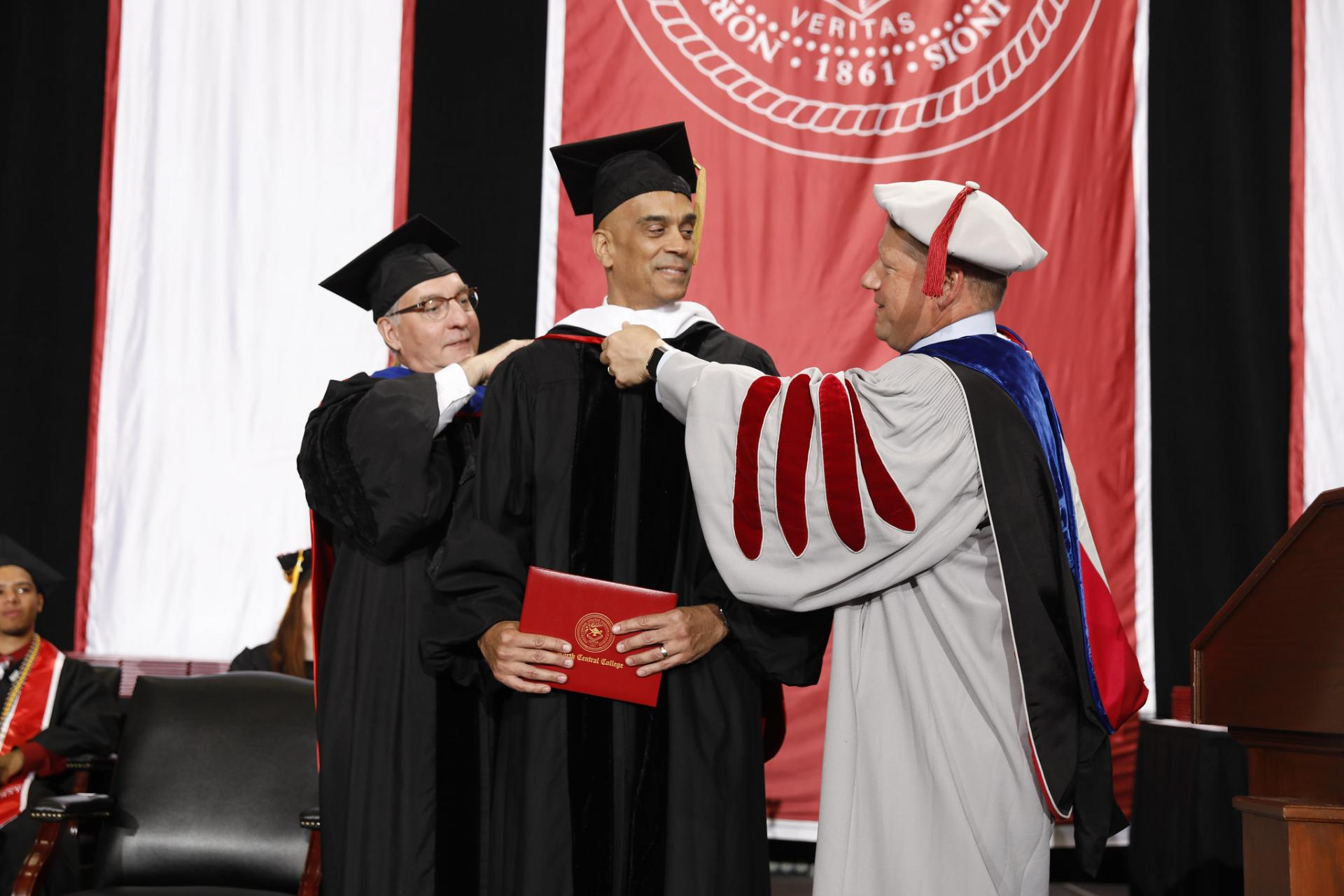 North Central College Commencement speaker Jim Williams is hooded by Board of Trustees Chair Jim McDermet and President Troy Hammond.