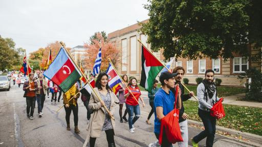 International club carrying flags during homecoming parade