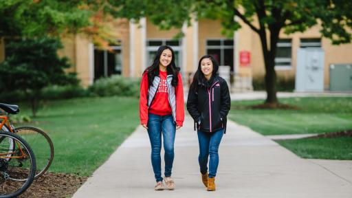 Two students waking through campus