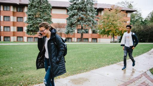 Student walking on campus talking on the phone