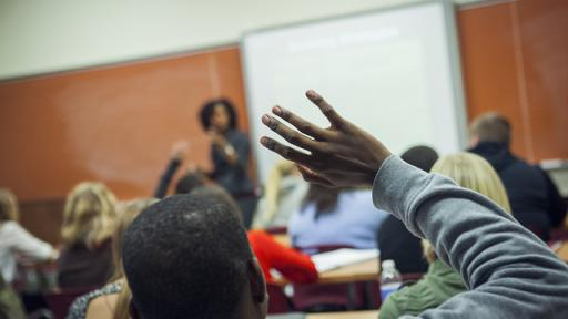 A student raising his hand to ask a question.