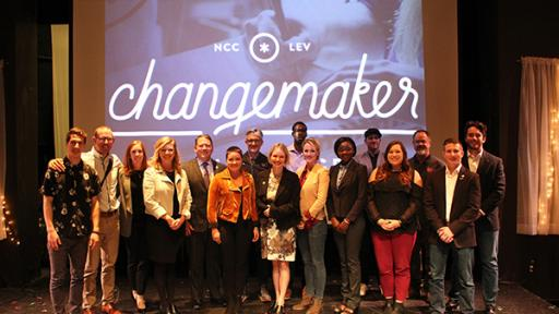 Students and faculty posing on stage at the Changemaker Challenge.