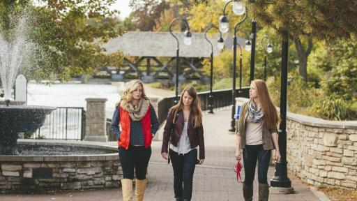 students walking along the riverwalk in downtown naperville