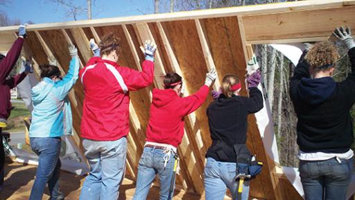 Students raising a wall at a Habitat for Humanity project.
