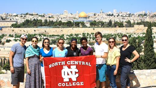 A group of North Central students holding up a College banner on a service trip to Israel.